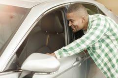 Przystojny Afrykański mężczyzna wybiera nowego samochód przy przedstawicielstwem handlowym obraz royalty free