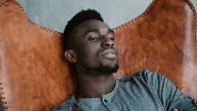 Przystojny Afrykański mężczyzna z brodą jest siedzący w ono uśmiecha się i krześle Samiec patrzeje marzycielską, rozważną i spoko Zdjęcie Stock
