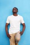 Przystojny amerykanina afrykańskiego pochodzenia mężczyzna przeciw błękit ścianie i przyglądającemu up Obrazy Stock