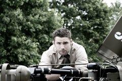Przystojny amerykanina WWII gi dowóca wojskowy w jednolitym i staczający się w górę rękawów obok łamanego puszka Willy dżipa fotografia royalty free