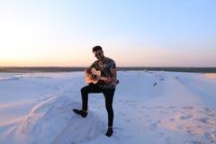 Przystojny Arabski facet bawić się gitarę, stoi na wzgórzu wśród piaska Obrazy Stock