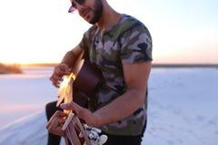 Przystojny Arabski facet bawić się gitarę, stoi na wzgórzu wśród piaska Obraz Stock