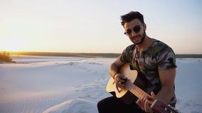 Przystojny Arabski facet bawić się gitarę, stoi na wzgórzu wśród piaska Zdjęcia Royalty Free
