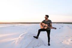 Przystojny Arabski facet bawić się gitarę, stoi na wzgórzu wśród piaska Fotografia Royalty Free