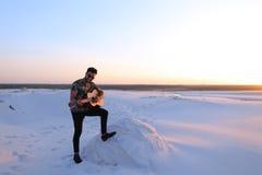 Przystojny Arabski facet bawić się gitarę, stoi na wzgórzu wśród piaska Zdjęcie Royalty Free