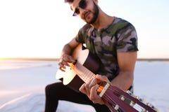 Przystojny Arabski facet bawić się gitarę, stoi na wzgórzu wśród piaska Obrazy Royalty Free