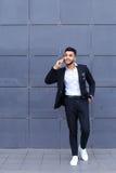 Przystojny arabski mężczyzna opowiada na mądrze telefonie w centrum biznesu Obrazy Stock