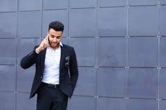 Przystojny arabski mężczyzna opowiada na mądrze telefonie w centrum biznesu Obraz Royalty Free