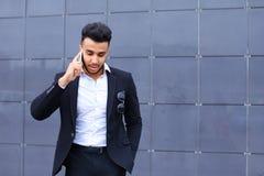 Przystojny arabski mężczyzna opowiada na mądrze telefonie w centrum biznesu Zdjęcia Royalty Free