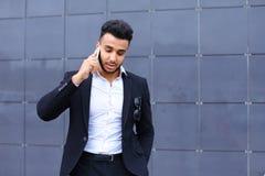 Przystojny arabski mężczyzna opowiada na mądrze telefonie w centrum biznesu Obrazy Royalty Free