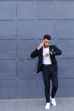 Przystojny arabski mężczyzna opowiada na mądrze telefonie w centrum biznesu Zdjęcie Royalty Free