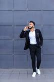 Przystojny arabski mężczyzna opowiada na mądrze telefonie w centrum biznesu Zdjęcia Stock