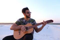 Przystojny Arabski młody człowiek przystosowywa gitarę, siedzi na wzgórzu w mi Zdjęcie Royalty Free