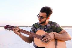 Przystojny Arabski młody człowiek przystosowywa gitarę, siedzi na wzgórzu w mi Obrazy Stock
