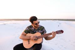 Przystojny Arabski młody człowiek przystosowywa gitarę, siedzi na wzgórzu w mi Zdjęcia Royalty Free