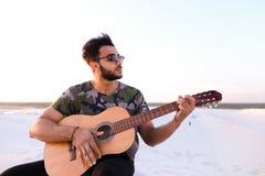 Przystojny Arabski młody człowiek przystosowywa gitarę, siedzi na wzgórzu w mi Zdjęcia Stock