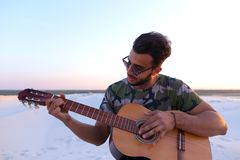 Przystojny Arabski młody człowiek przystosowywa gitarę, siedzi na wzgórzu w mi Fotografia Stock