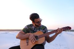 Przystojny Arabski młody człowiek przystosowywa gitarę, siedzi na wzgórzu w mi Obraz Stock