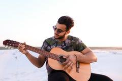 Przystojny Arabski młody człowiek przystosowywa gitarę, siedzi na wzgórzu w mi Obrazy Royalty Free