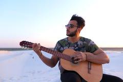 Przystojny Arabski młody człowiek przystosowywa gitarę, siedzi na wzgórzu w mi Zdjęcie Stock