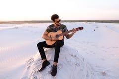 Przystojny Arabski młody człowiek przystosowywa gitarę, siedzi na wzgórzu w mi Fotografia Royalty Free