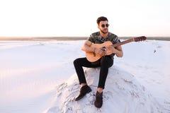 Przystojny Arabski młody człowiek przystosowywa gitarę, siedzi na wzgórzu w mi Obraz Royalty Free