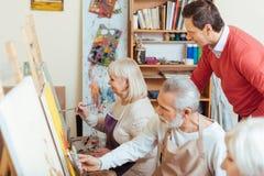 Przystojny artysta kontroluje jego kolegów w obraz klasie zdjęcia stock