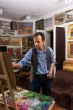 Przystojny artysta w trakcie malować jego arcydzieło Obrazy Royalty Free