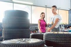 Przystojny auto mechanik pomaga klienta wybierać od różnorodnych opon Zdjęcie Royalty Free