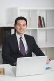 Przystojny Azjatycki biznesmen przy pracą z laptopem na t obrazy stock
