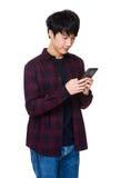 Przystojny azjatykci facet siedzi wiadomość na jego smartphone i czyta Obraz Royalty Free