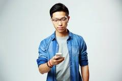 Przystojny azjatykci mężczyzna używa smartphone zdjęcie royalty free