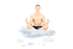 Przystojny bez koszuli mężczyzna medytuje na chmurach fotografia royalty free