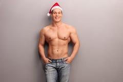 Przystojny bez koszuli mężczyzna z Santa kapeluszem zdjęcia stock