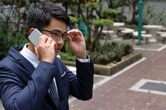 Przystojny biznesmen opowiada na jego telefonie komórkowym w miasto parku Obrazy Royalty Free