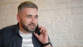 Przystojny biznesmen opowiada na telefonie przy kawiarnią Młody brodaty facet trzyma jego smartphone blisko jego ucho atrakcyjny zdjęcie wideo