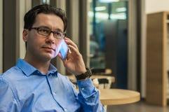 Przystojny biznesmen opowiada na telefonie w kawiarni fotografia royalty free