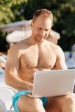 Przystojny biznesmen pracuje na jego laptopu pobliskim basenie obrazy royalty free