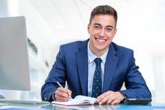Przystojny biznesmen przy biurkiem w biurze Obraz Stock