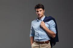 Przystojny biznesmen trzyma jego kurtkę nad ramieniem Zdjęcie Stock