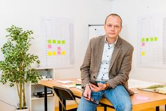 Przystojny biznesmen Trzyma Smartphone Przy biurem obraz royalty free