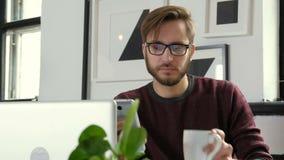 Przystojny biznesmen używa smartphone i ono uśmiecha się podczas gdy pracujący w biurze 20s 4k zbiory wideo