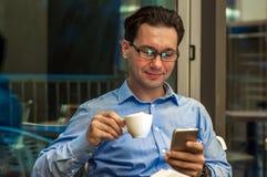 Przystojny biznesmen w eyeglasses używa smartphone, trzyma filiżankę kawy i ono uśmiecha się, podczas gdy stojący blisko okno zdjęcie royalty free