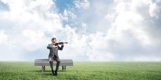 Przystojny biznesmen w parku na drewnianej ławki sztuce jego melodia obrazy royalty free