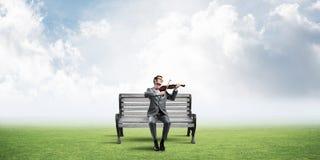 Przystojny biznesmen w parku na drewnianej ławki sztuce jego melodia zdjęcie royalty free