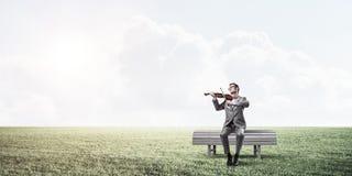 Przystojny biznesmen w parku na drewnianej ławki sztuce jego melodia fotografia royalty free
