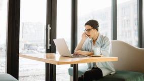 Przystojny biznesmen w przypadkowej odzieży i eyeglasses używa laptop w kawiarni Obraz Royalty Free