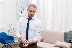 Przystojny biznesmena kładzenie na zegarku zdjęcia stock