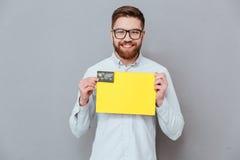 Przystojny biznesmena mienia copyspace puste miejsce i karta debetowa Zdjęcie Stock