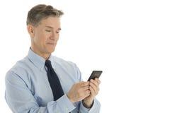 Przystojny biznesmena wysylanie sms Na telefonie komórkowym obraz stock